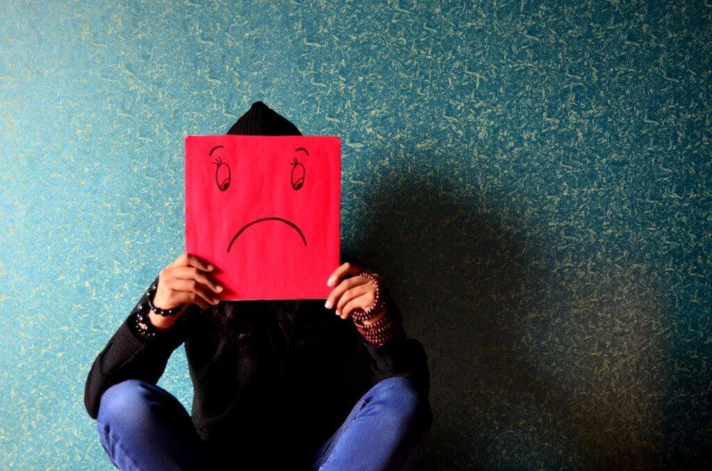Depressão Pós Parto: Pessoa sentada segurando placa com cara triste