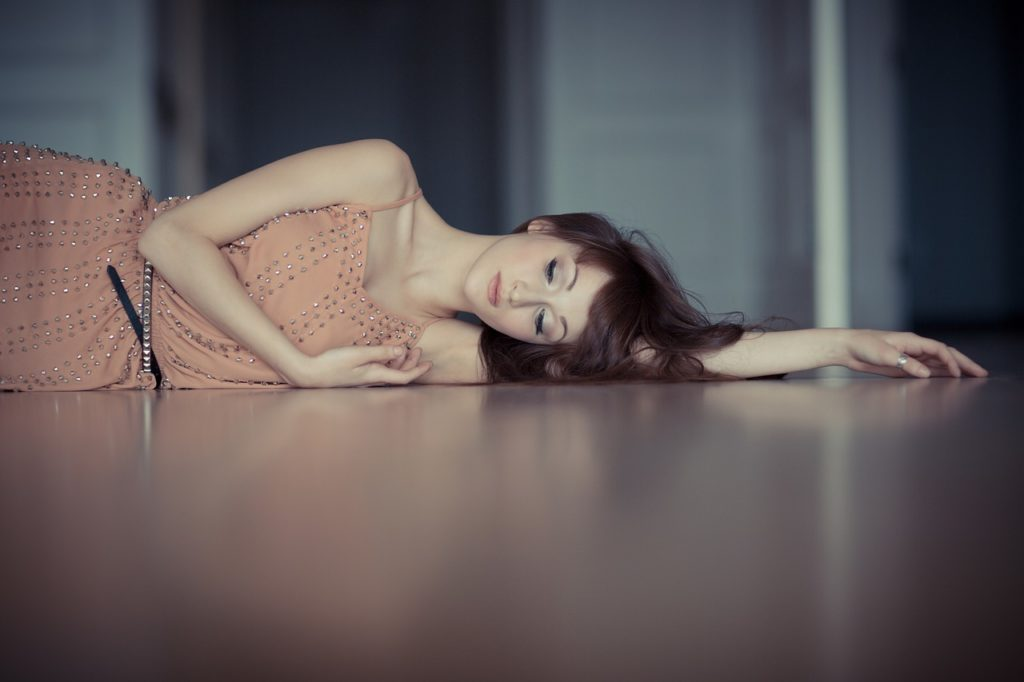 pressão para engravidar: mulher deitada de lado no chão.