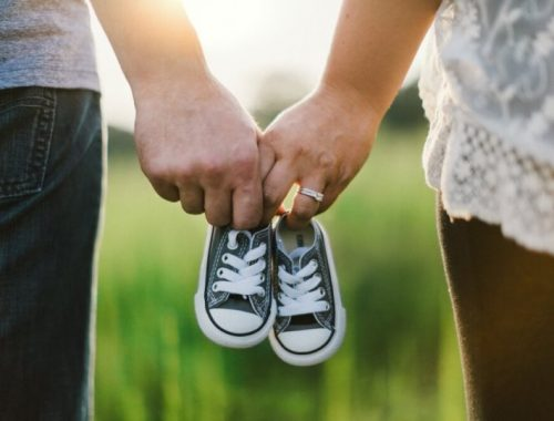 Casal Após Chegada do Bebê: Casal segurando sapatinho de bebê